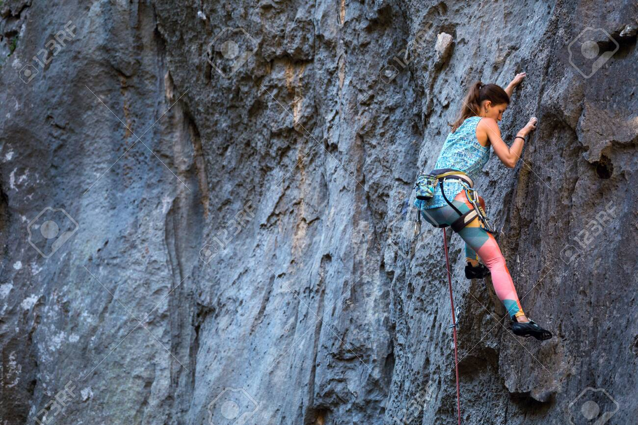 Climber overcomes challenging climbing route. A girl climbs a rock. Woman engaged in extreme sport. Extreme hobby. - 126950110
