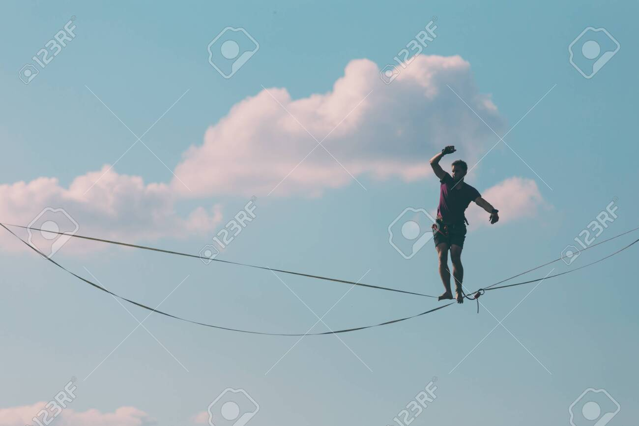 Highliner on the background of blue sky makes a move. A man is walking along a stretched sling. Performance tightrope walker. Man balances over the abyss. A decisive step forward. - 143332213