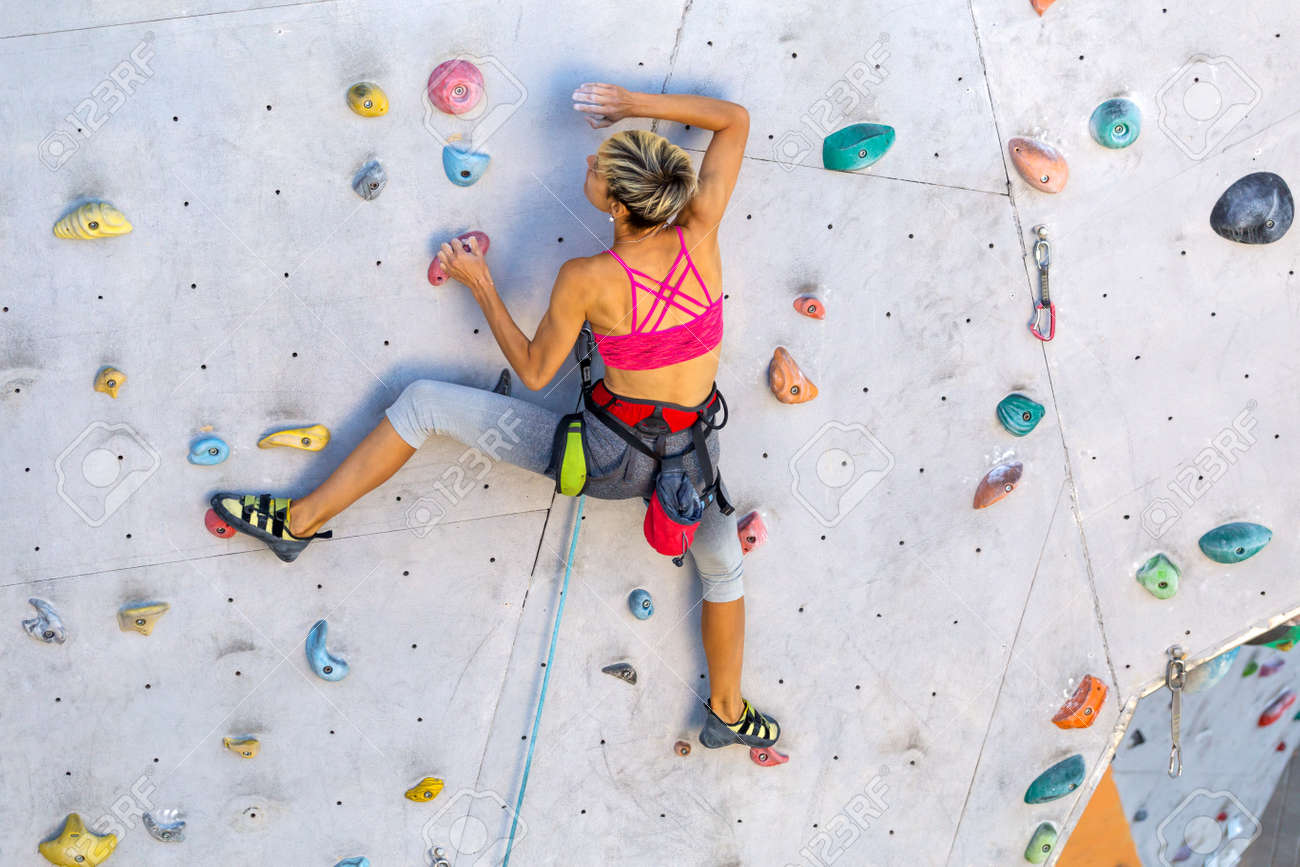 A woman climbs a climbing wall, a climber is training on artificial terrain, rock climbing in the city, a strong girl, sports in the city, safety in extreme sports. - 159874653