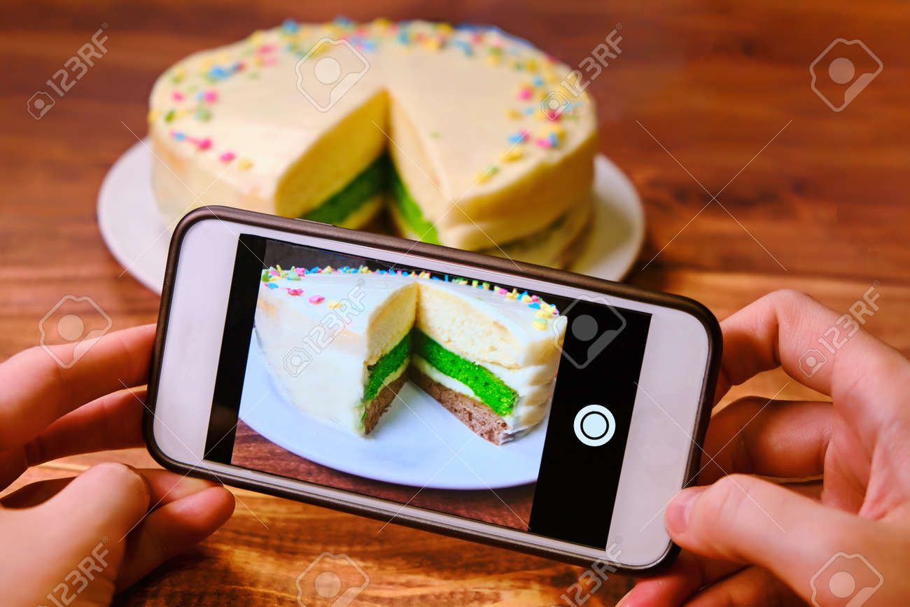 Women's hands with the phone taking pictures of the cake. Blogger shoots food . Create a photo for posting on the Internet. White phone and a tri-color cake on a wooden table. - 156788202