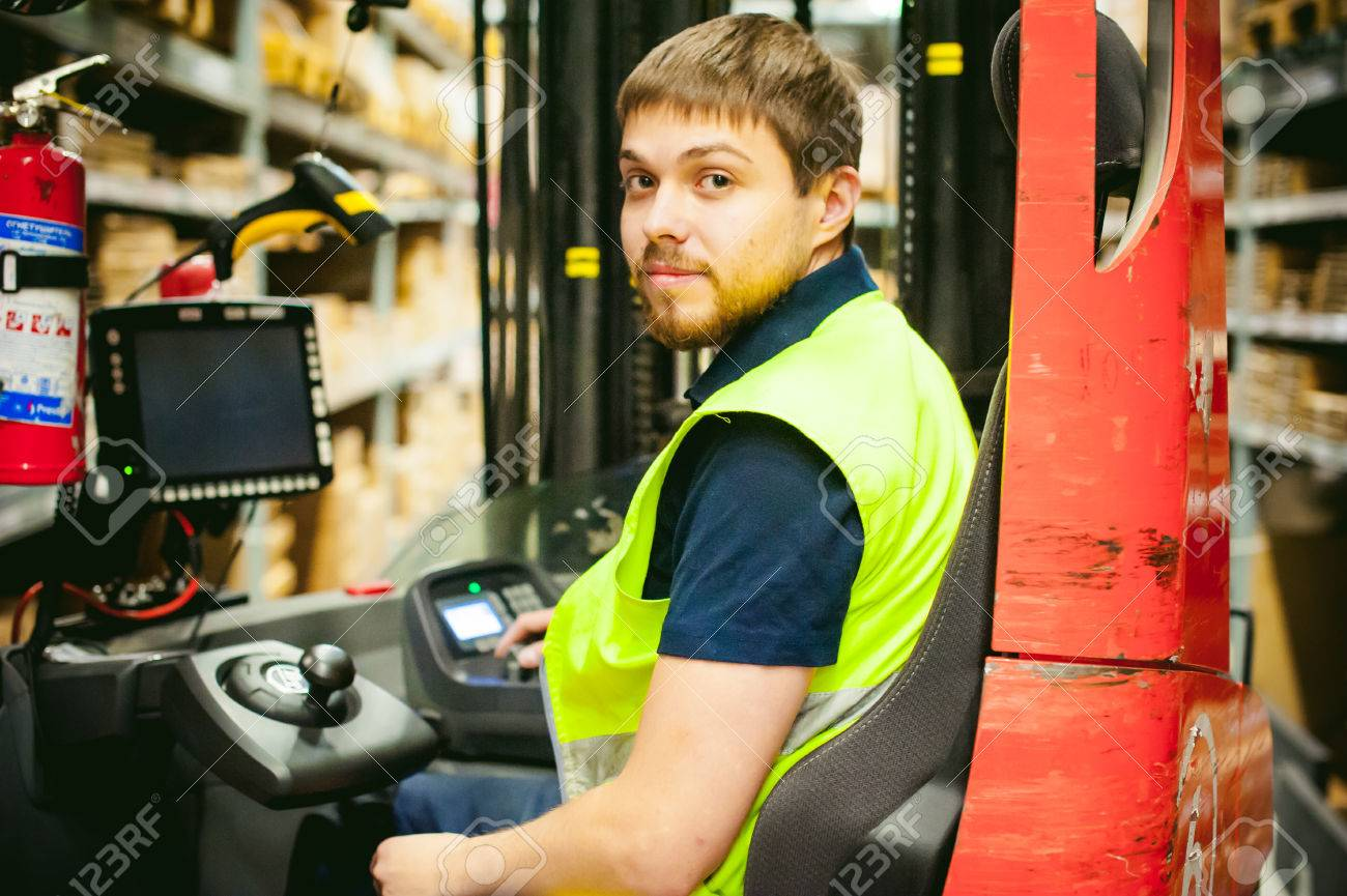 young man in working clothes, driver Reachtruck busy working on the logistics warehouse store - 68921715
