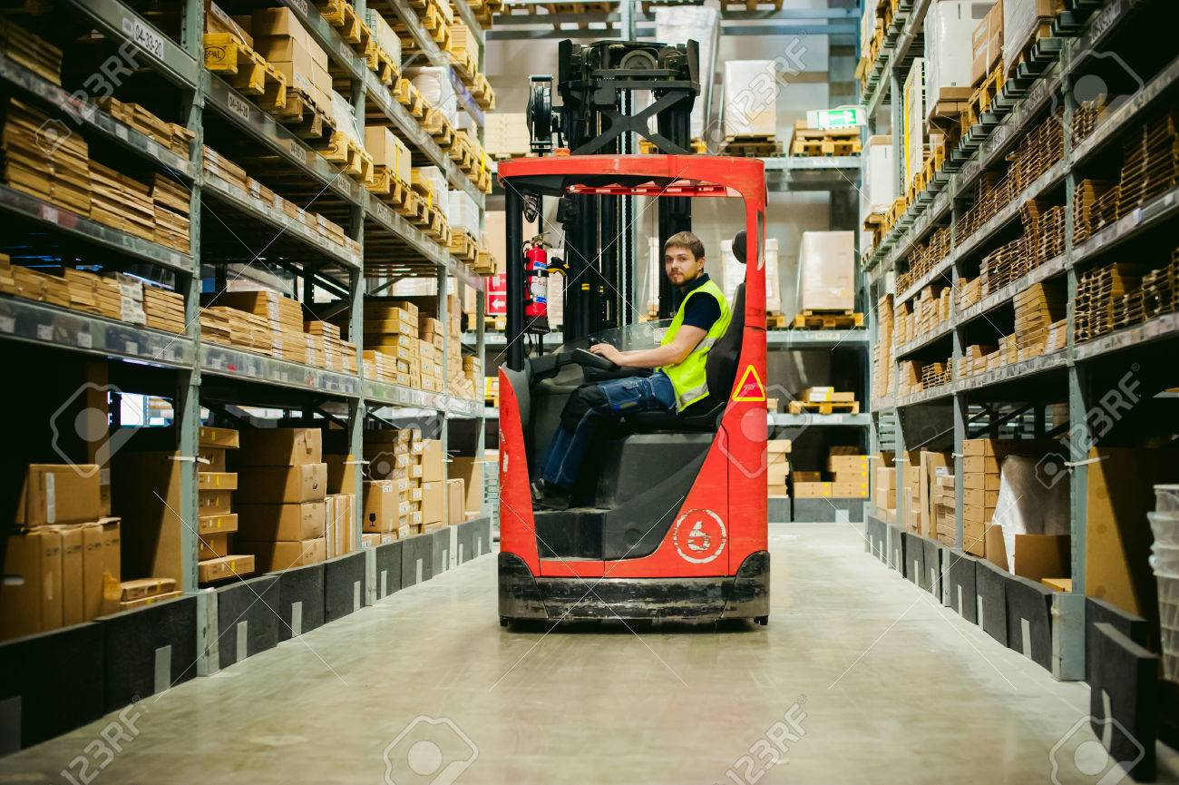 young man in working clothes, driver Reachtruck busy working on the logistics warehouse store - 68934263