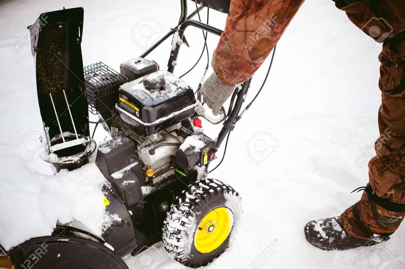 man starts the engine snow blower - 70182841