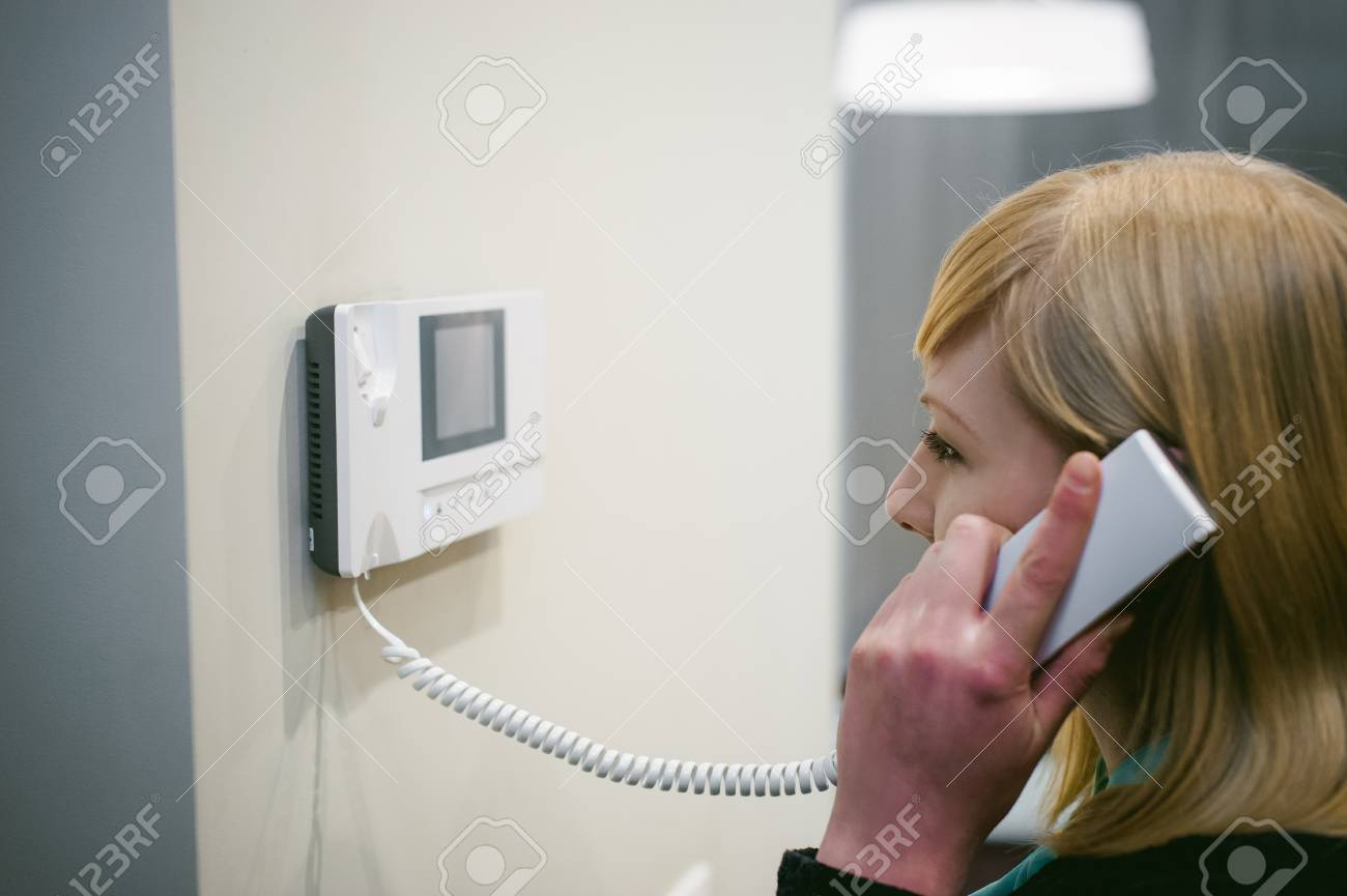 blonde woman answers the intercom call while holding the phone to your ear - 70949708