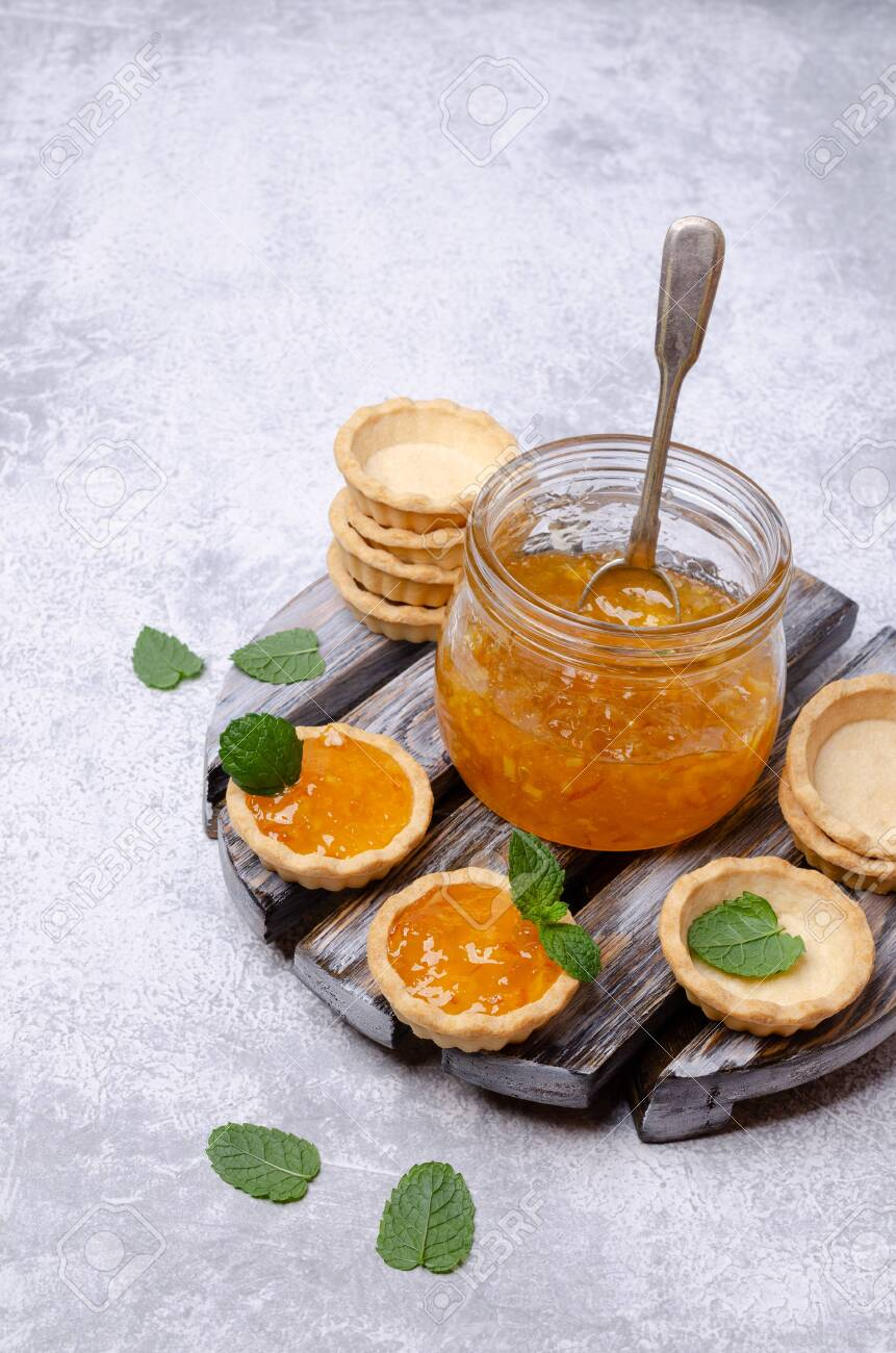 Tartlets with orange jam and mint on a slate background. Selective focus. - 126174240