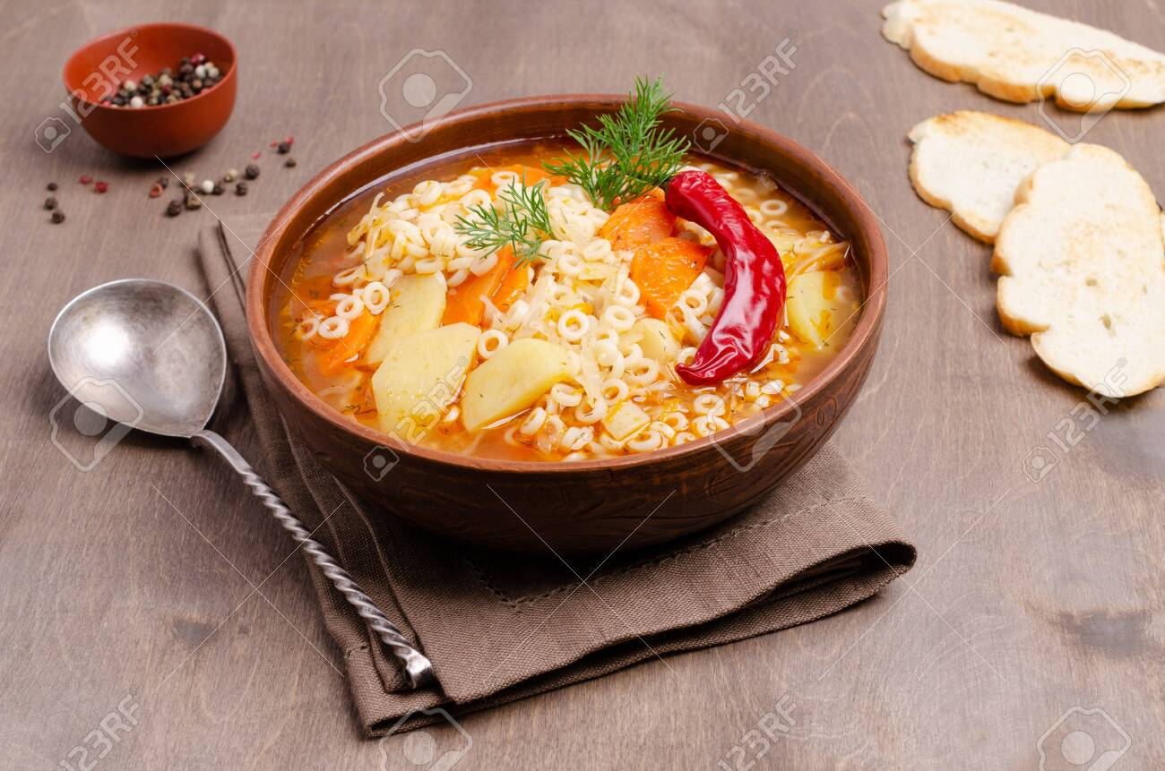 Thick vegetable soup with pasta in a ceramic bowl on a wooden background. Selective focus. - 129509514