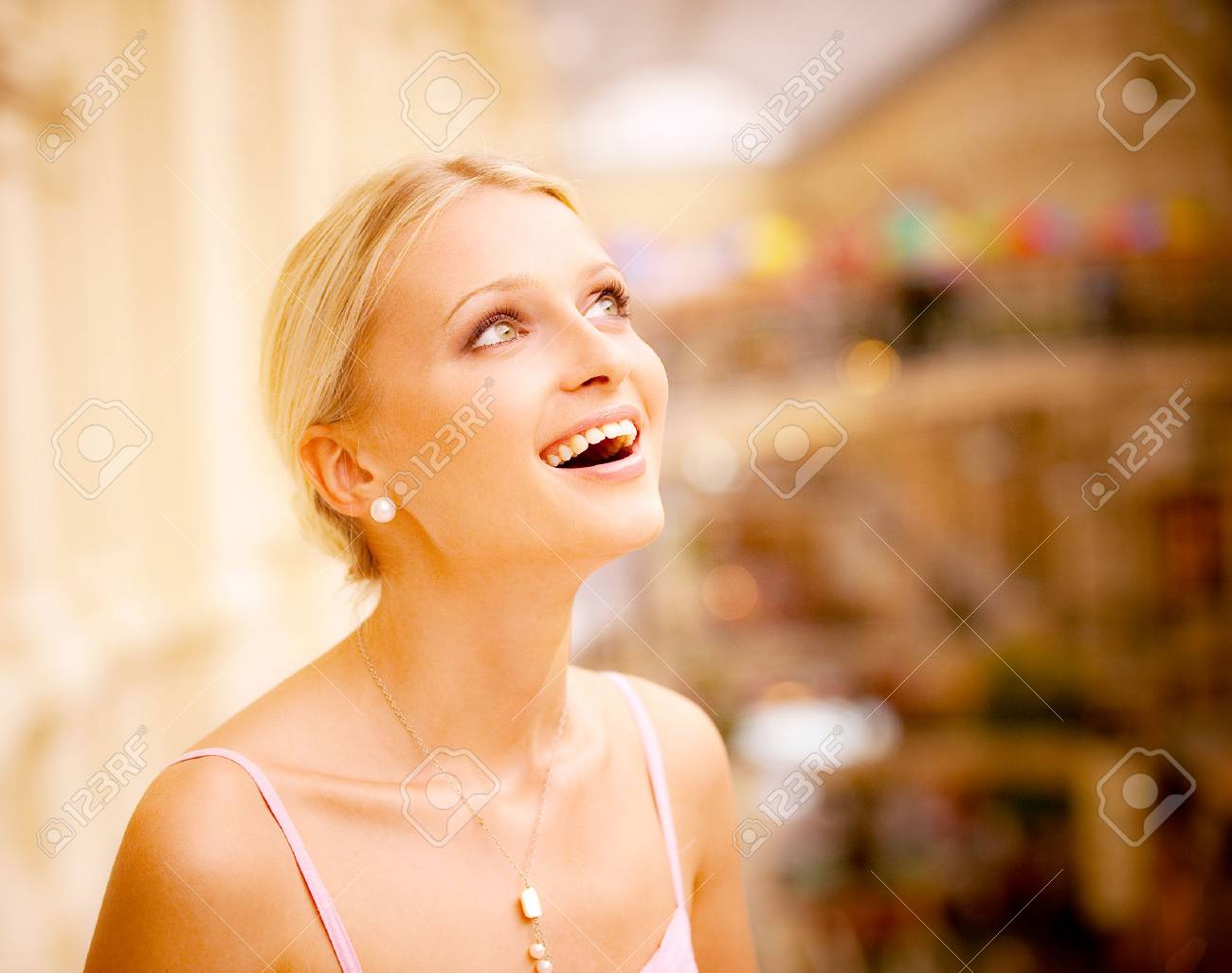 Charming girl looks upwards and laughs. In magnificent huge hall. Stock Photo - 6457222