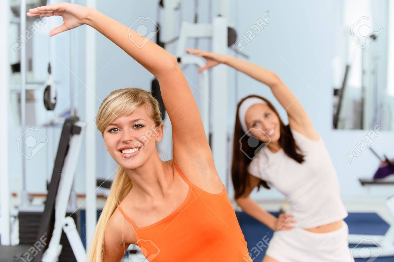 Two beautiful smiling sportswomen do exercises in big sports hall. Stock Photo - 7119952