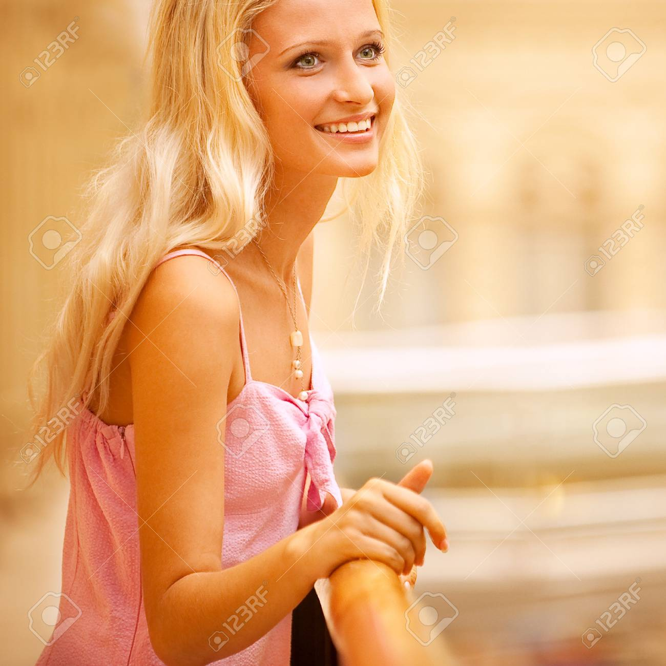 Beautiful girl leans against handrail in magnificent hall and laughs. Stock Photo - 8016494