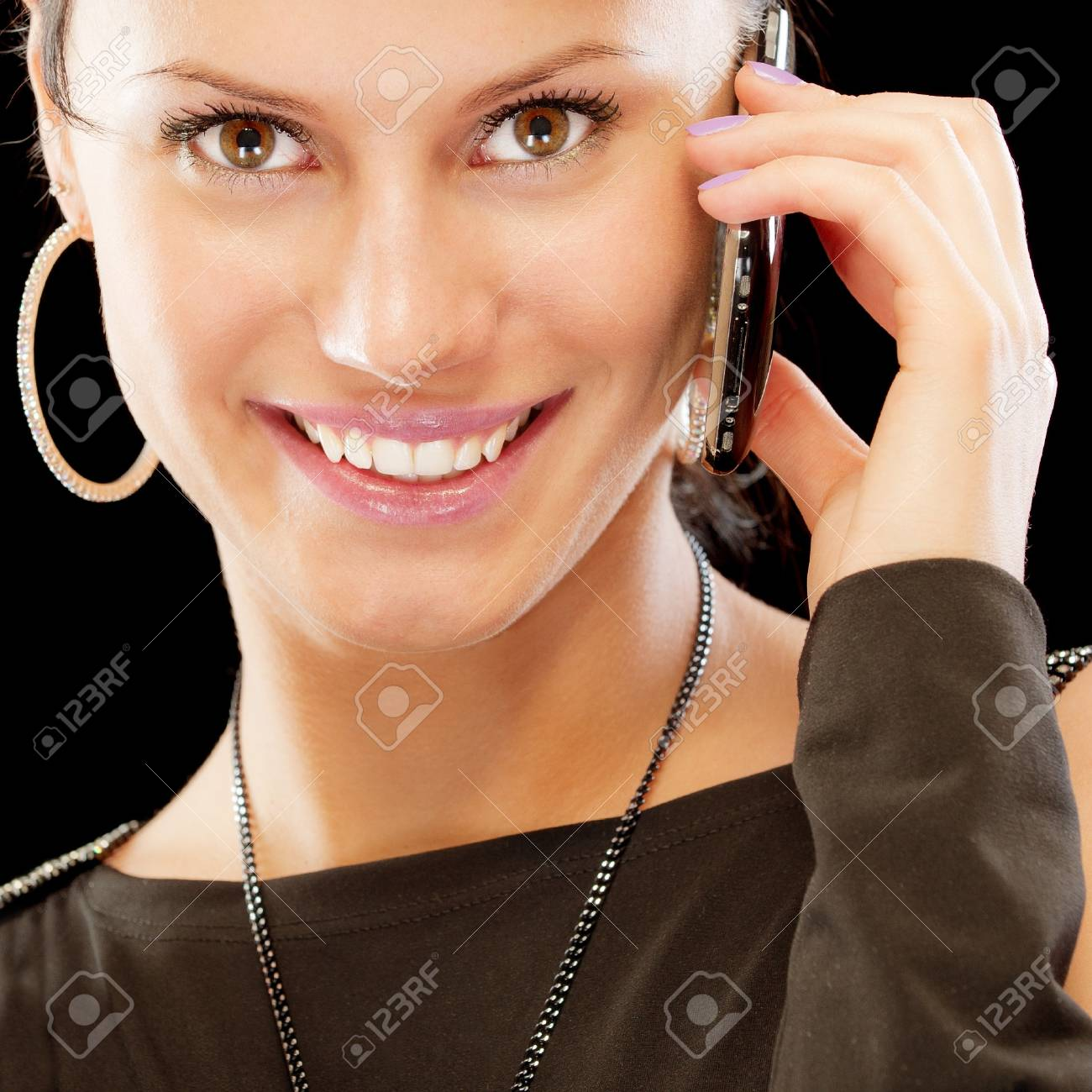 Smiling brunette speaks by mobile phone, isolated on black background. Stock Photo - 8016504