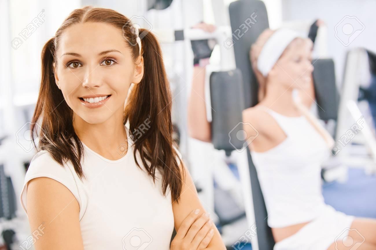 Two beautiful sportwomen make exercise on training apparatus Stock Photo - 8090483