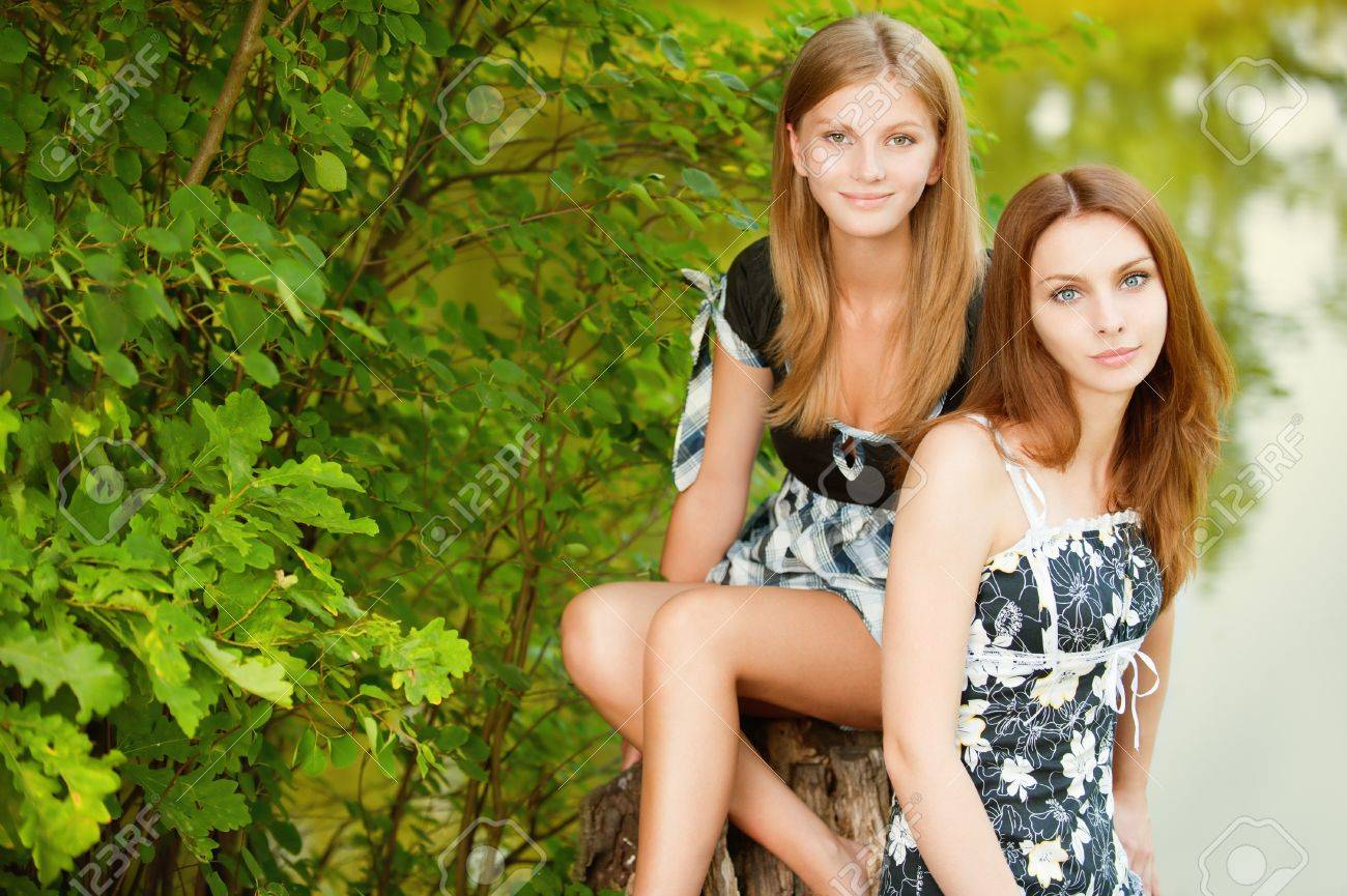 Two beautiful girls sit on stub about pond in summer city park. Stock Photo - 9372059