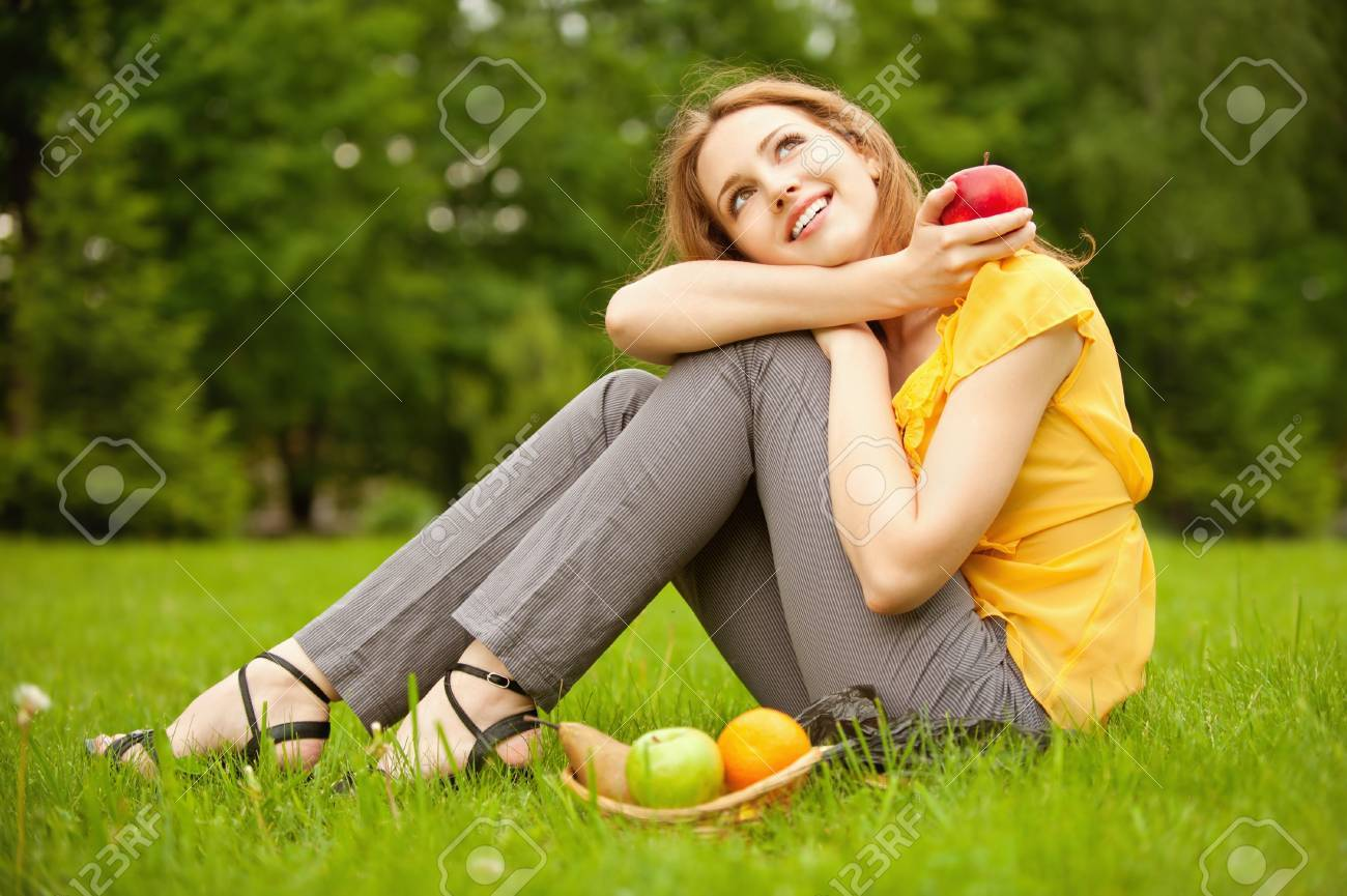Portrait of girl with basket apples against green grass. Stock Photo - 9591044