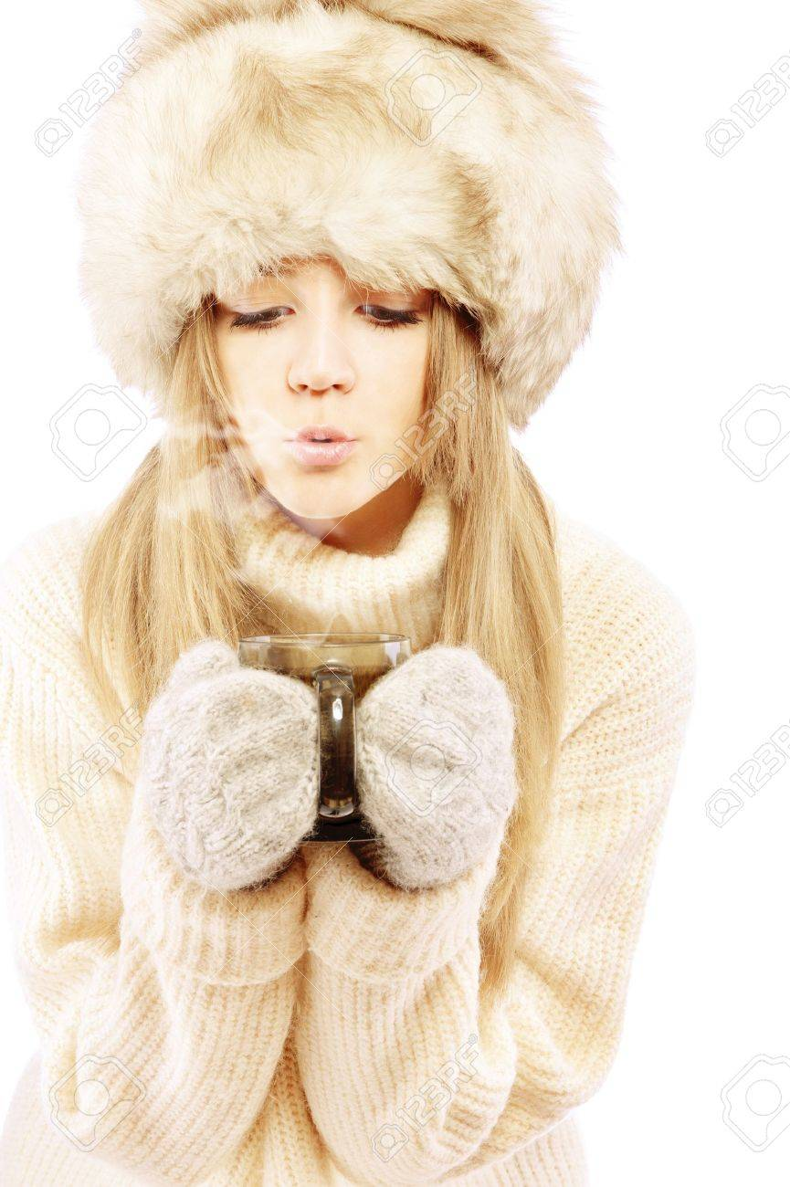 Beautiful young woman in fur cap and sweater blows on hot tea, isolated on white background. Stock Photo - 9659224