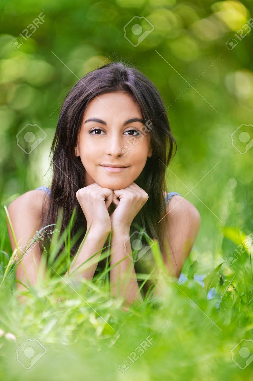 portrait of beautiful young long-haired woman lying on grass in park and propping up her face with hands Stock Photo - 9980671