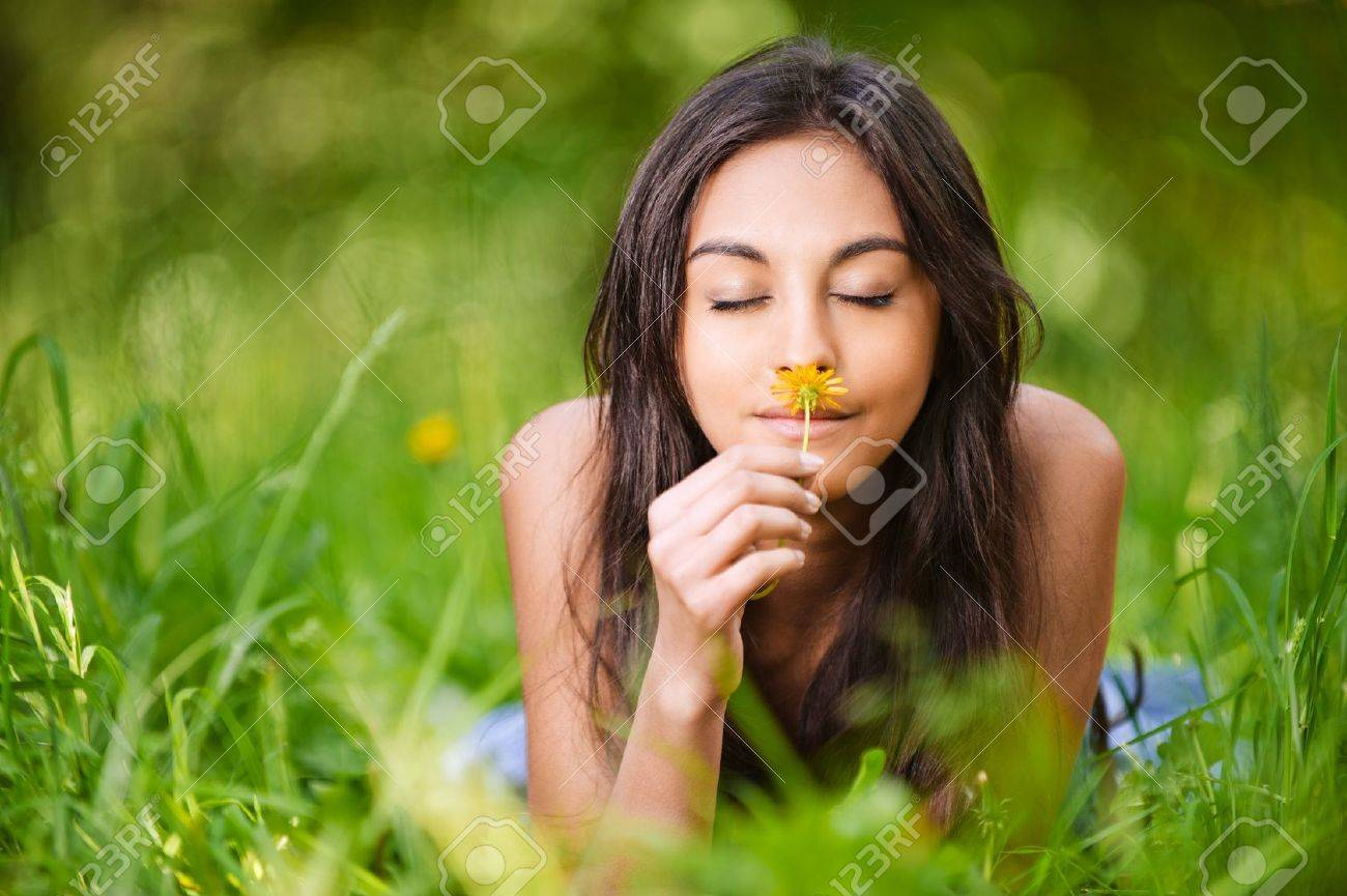 portrait of beautiful young long-haired woman lying in park and smelling flowers Stock Photo - 9980676