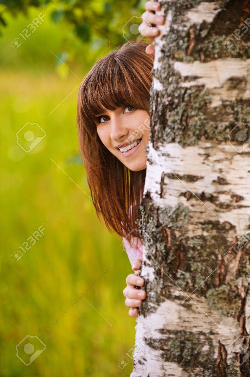Portrait of young attractive funny smiling dark-haired girl looking from behind birch tree at summer green park. Stock Photo - 9980719
