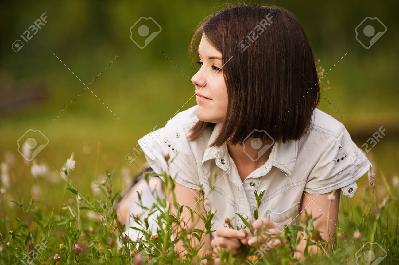 Portrait of young beautiful pensive dreamy girl lying on grass at summer green park. Stock Photo - 9980779