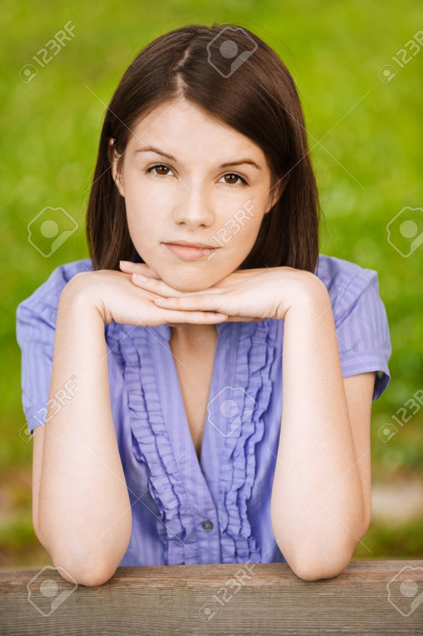 Portrait of young beautiful brunette woman propping up her face and wearing blue blouse at summer green park. Stock Photo - 9980773