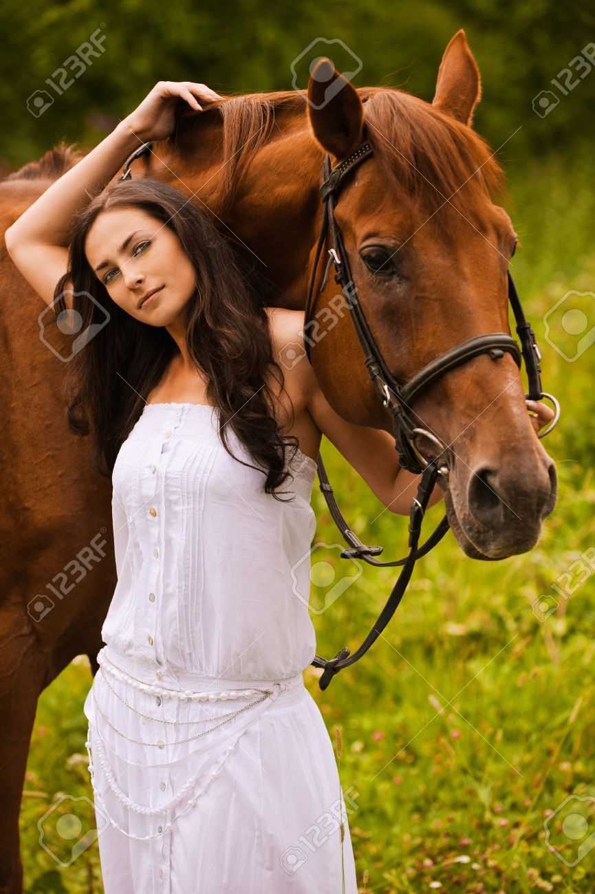 Portrait of young beautiful woman wearing white dress standing at summer green park with brown kind horse. Stock Photo - 9980807
