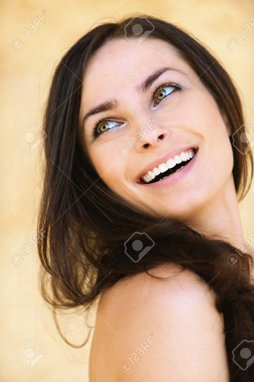 Close-up portrait of young attractive brunette smiling woman looking somewhere against yellow background. Stock Photo - 9980784