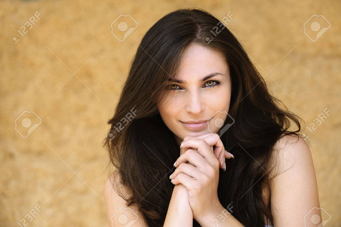 Portrait of young alluring smiling attractive brunnete woman propping up her face against yellow background. Stock Photo - 9980800