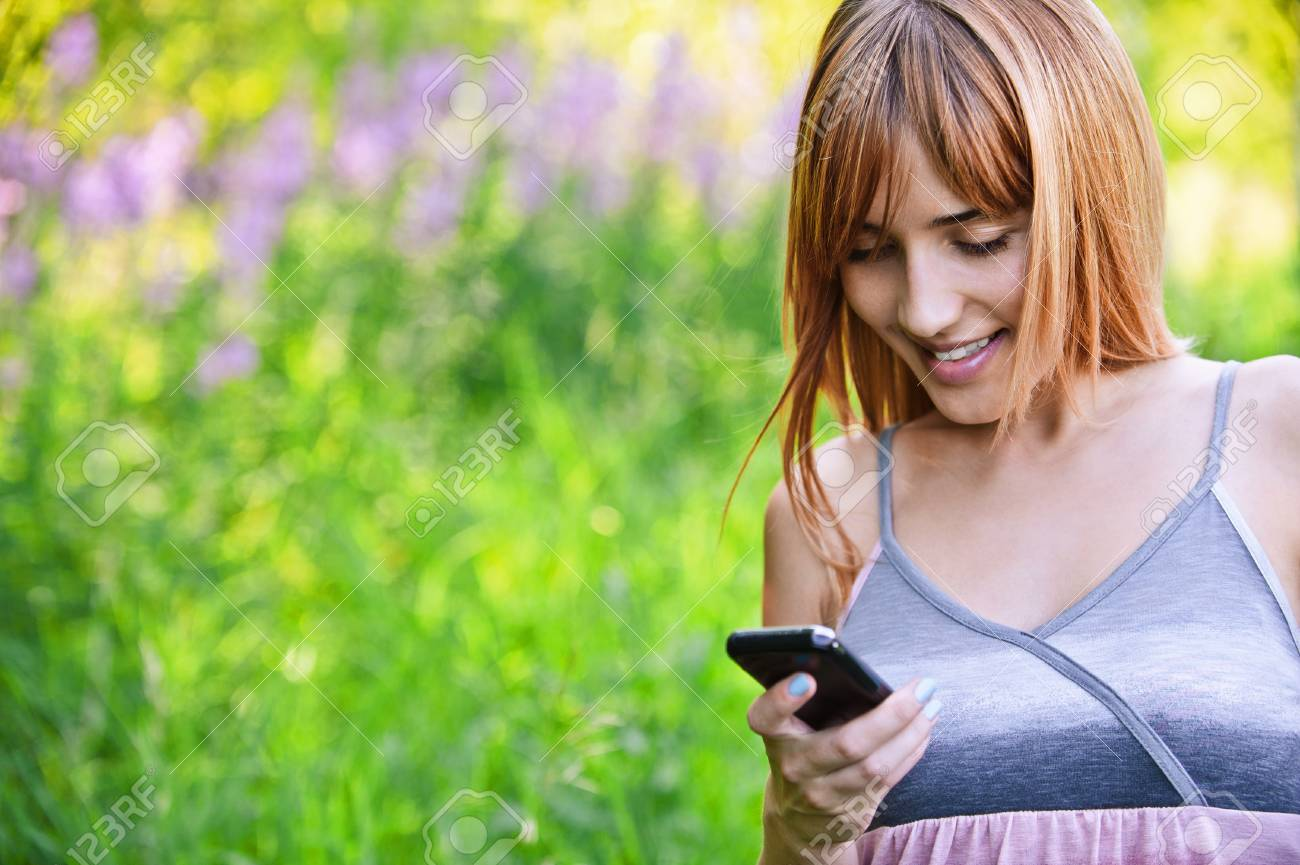 Portrait of young smiling woman holding mobile phone at summer green park. Stock Photo - 9980822
