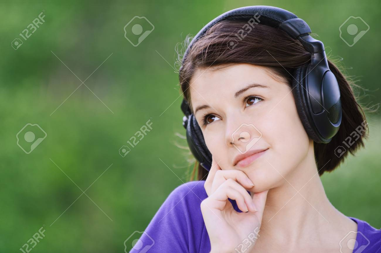 Close-up portrait of young beautiful brunette woman wearing headphones and propping up her face at summer green park. Stock Photo - 9980990