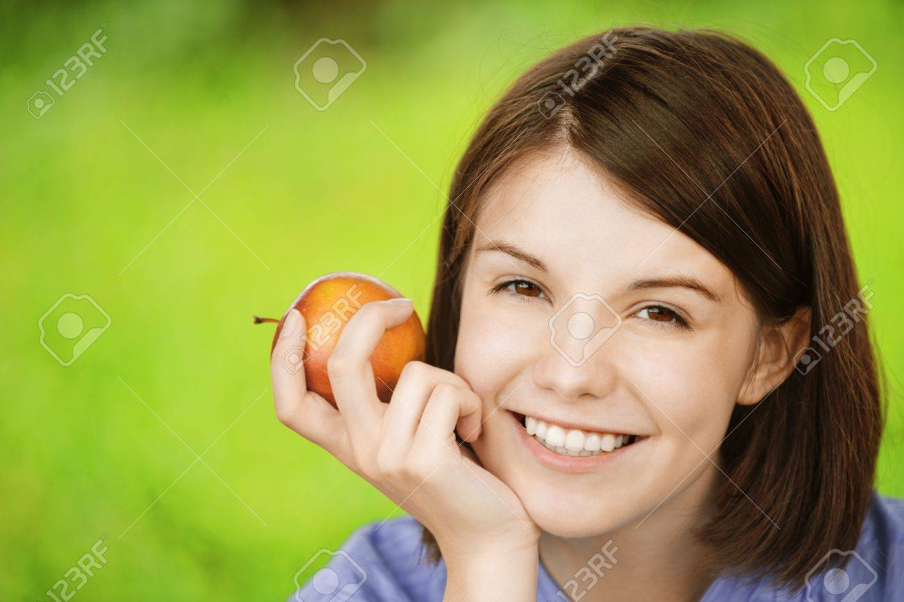 Close-up portrait of young smiling brunette woman holding red apple at summer green park. Stock Photo - 9980944