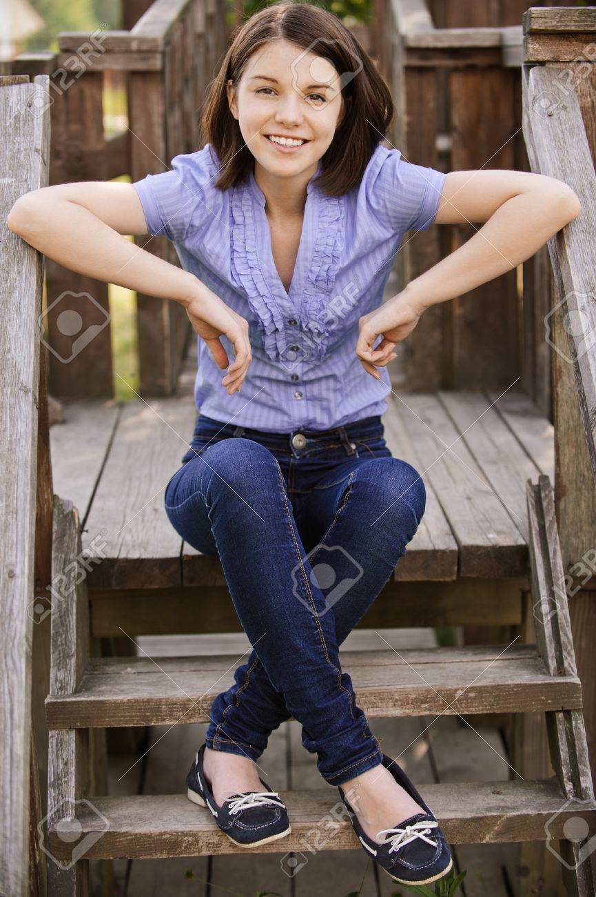 Young beautiful dark-haired smiling woman wearing blue blouse and jeans sitting on wooden staircase at summer park. Stock Photo - 9980970