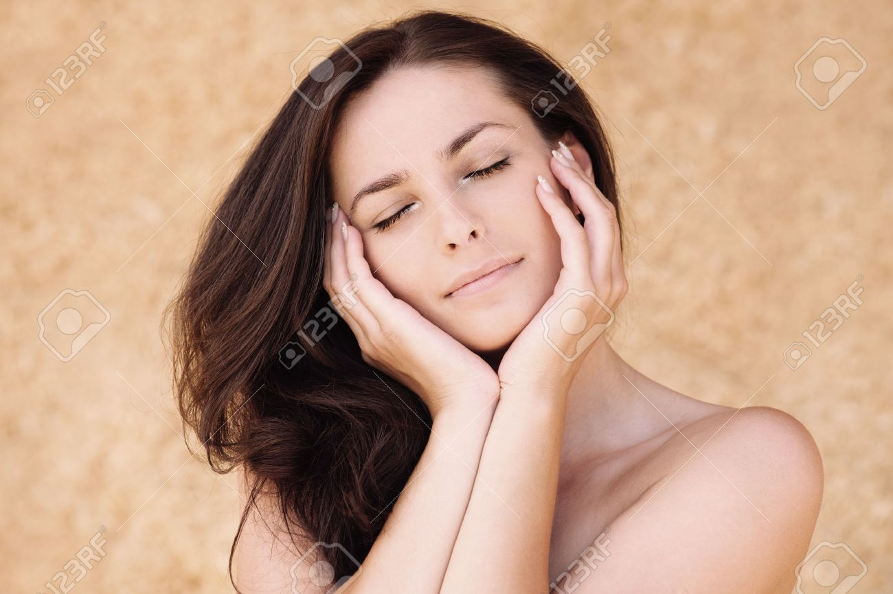 Portrait of young beautiful woman with eyes closed propping up her face against beige background. Stock Photo - 10194014