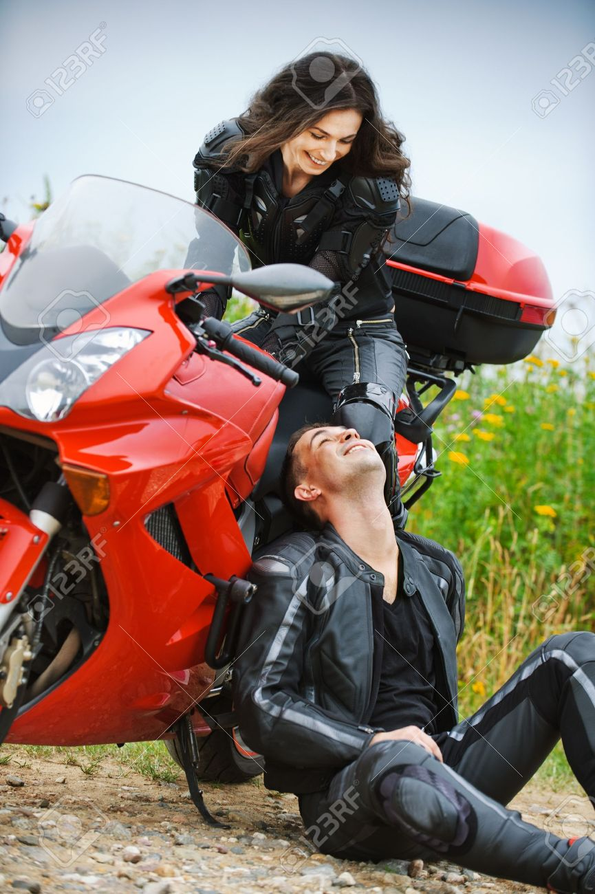 Two people: young beautiful woman sitting on motorbike and smiling man having rest. Stock Photo - 10341205
