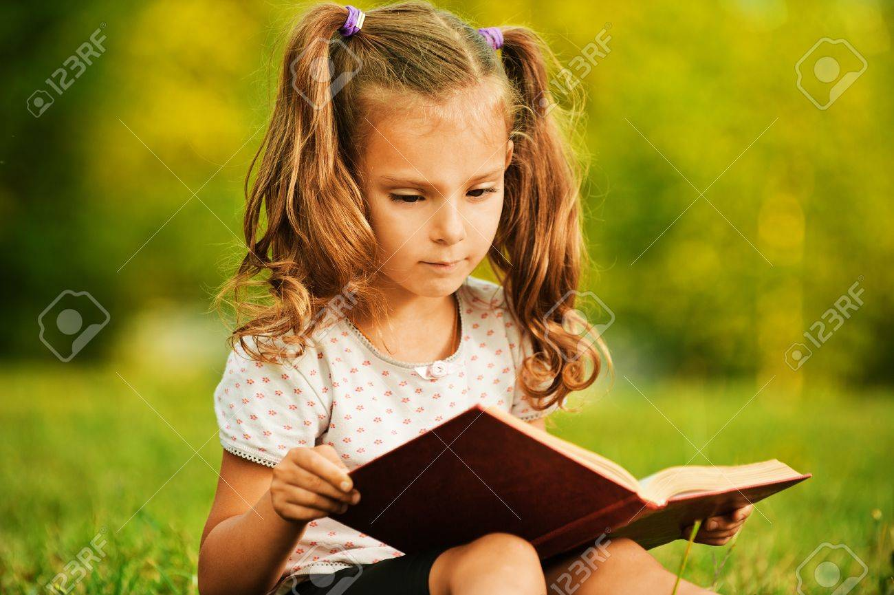Portrait of little cute fair-haired girl reading book, sitting at summer green park. Stock Photo - 10407254