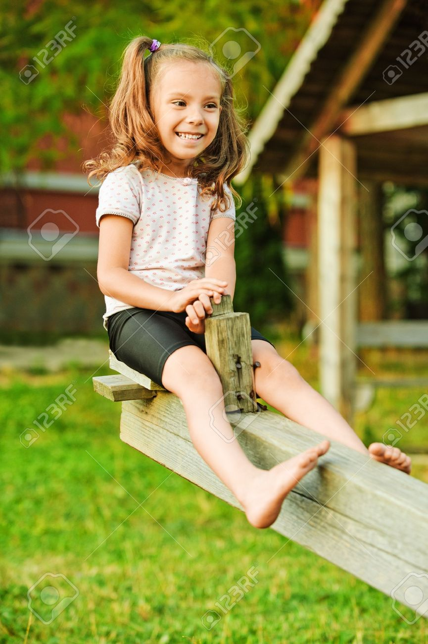 Portrait of little smiling girl wearing white t-shirt and shorts having fun on seesaw at summer green park. Stock Photo - 10407255