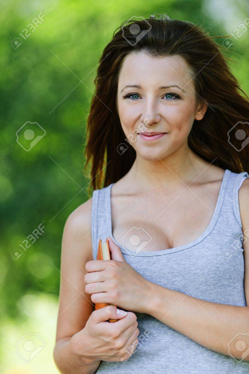 Portrait of pretty student girl wearing grey t-shirt, holding book at summer green park. Stock Photo - 10422283