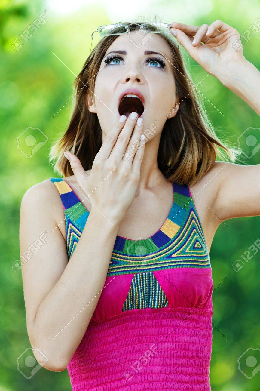 Portrait surprised girl looking up raising glasses pink dress Stock Photo - 10744329