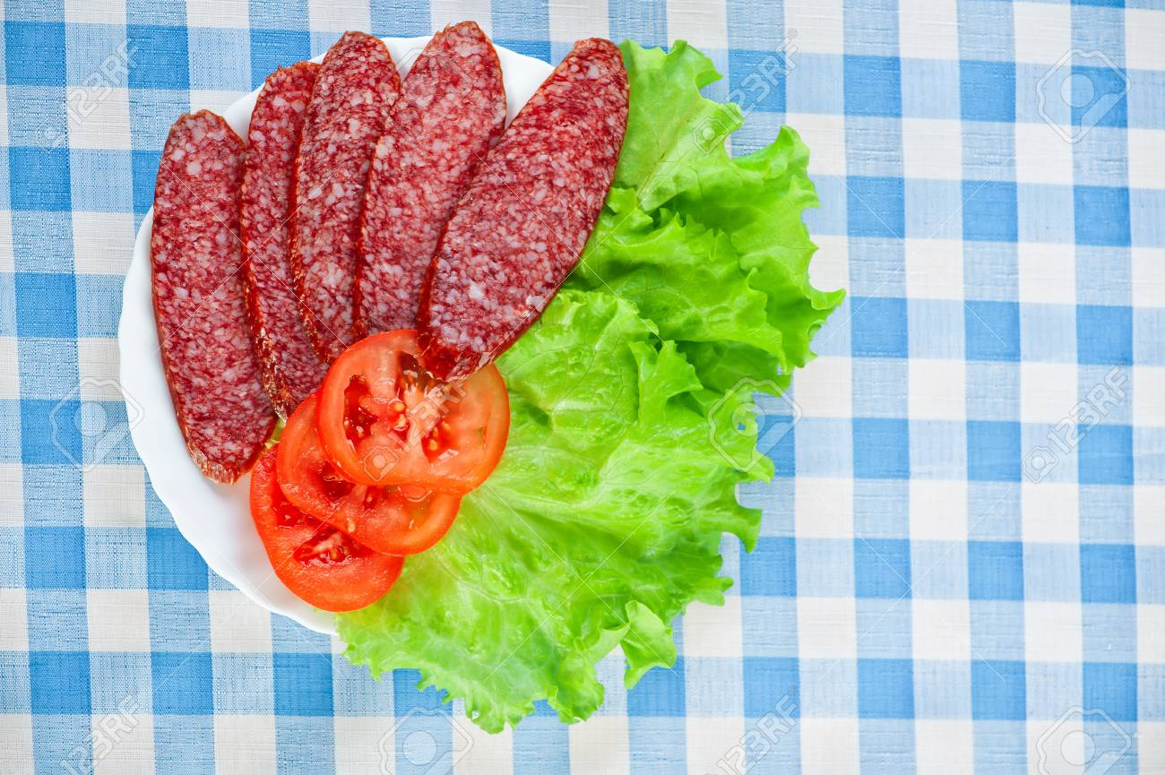 sliced ​​smoked sausage, tomatoes, lettuce background tablecloth Stock Photo - 11254863