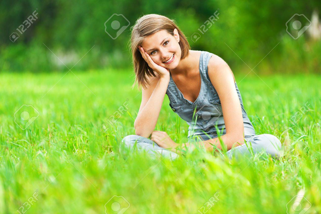 Portrait of pretty, young, cheerful woman sitting on green meadow (grass meadow) rests, legs crossed Stock Photo - 11742801