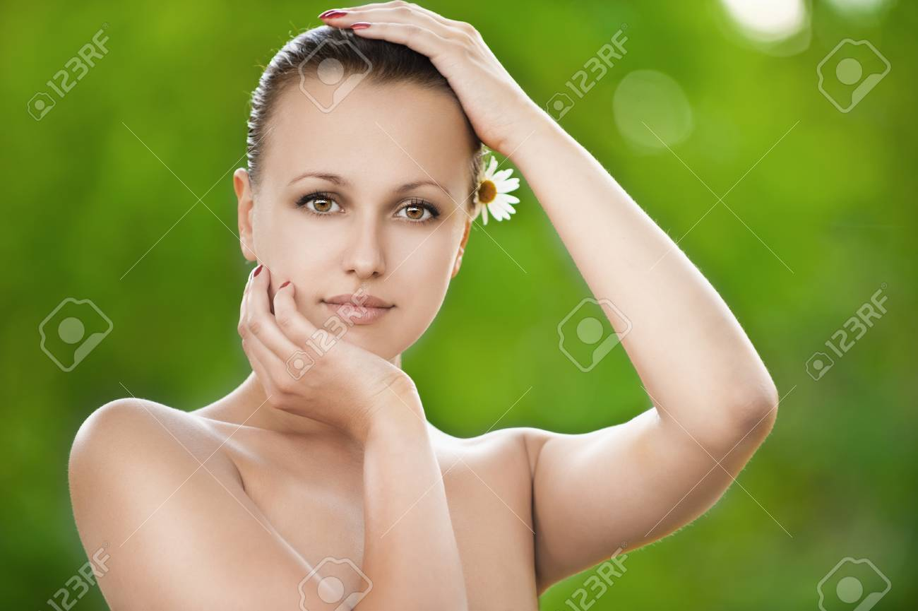 Portrait of beautiful young woman stroking her pretty face at summer green park Stock Photo - 12472485