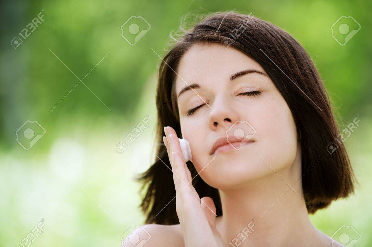 Close-up portrait of young beautiful brunette woman putting white cream on her face at summer green park Stock Photo - 12472811
