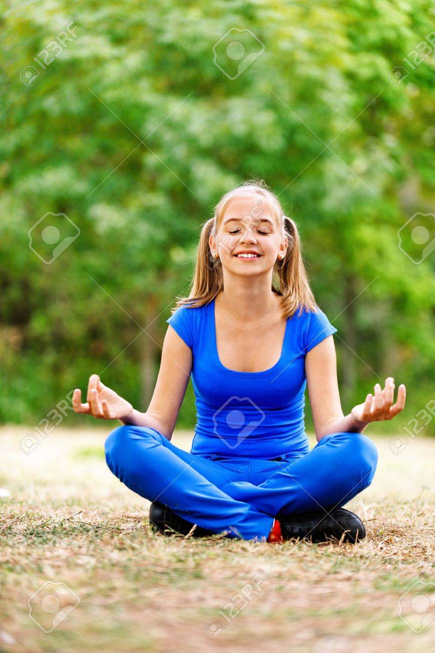 Smiling teenage girl in blue dress sitting in lotus position on green meadow in summer park. Stock Photo - 13004218