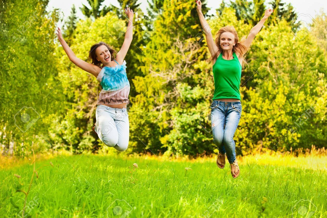 c933918e90f3 Dos chicas hermosas jóvenes salta en verano parque verde