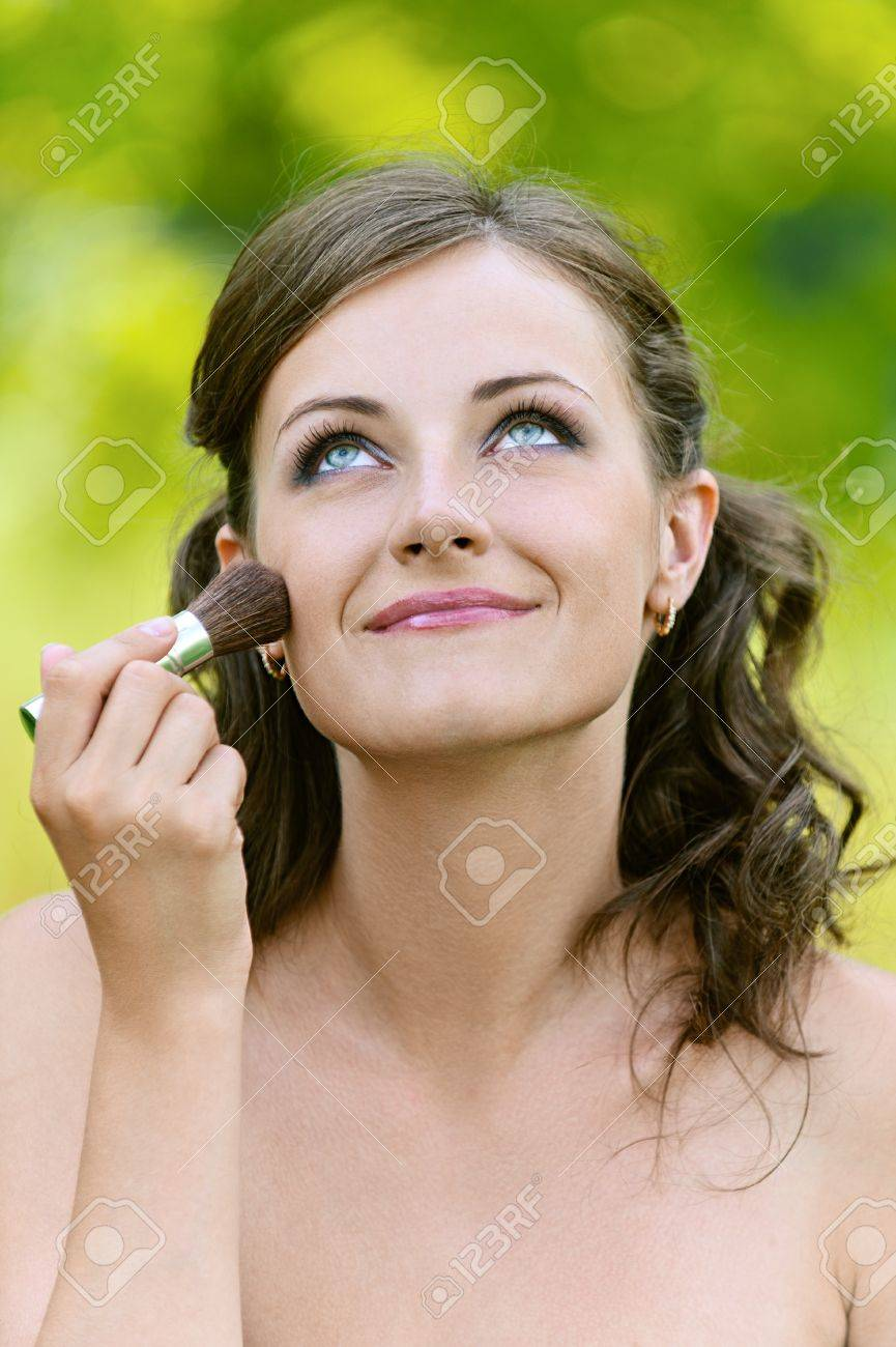 Beautiful young woman close up puts on her face powder brush, against green of summer park. Stock Photo - 14720060