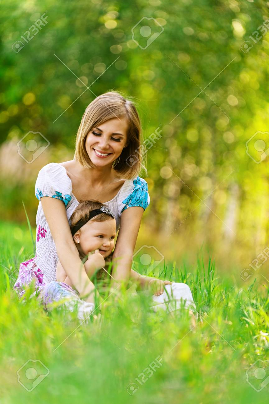 Portrait of smiling beautiful young woman and her little daughter sitting on grass, against green of summer park. Stock Photo - 14720064