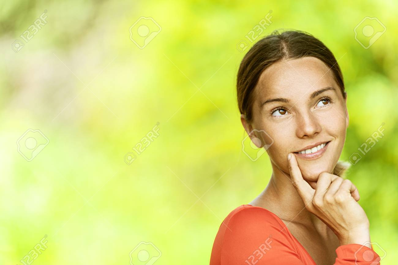 Portrait of dark-haired pensive beautiful young woman in red blouse close up, against green of summer park. Stock Photo - 14943028