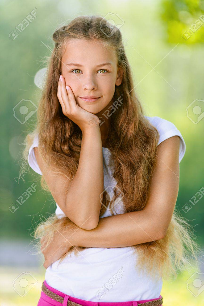 Portrait of beautiful smiling teenage girl in white blouse, against green of summer park. Stock Photo - 15282493
