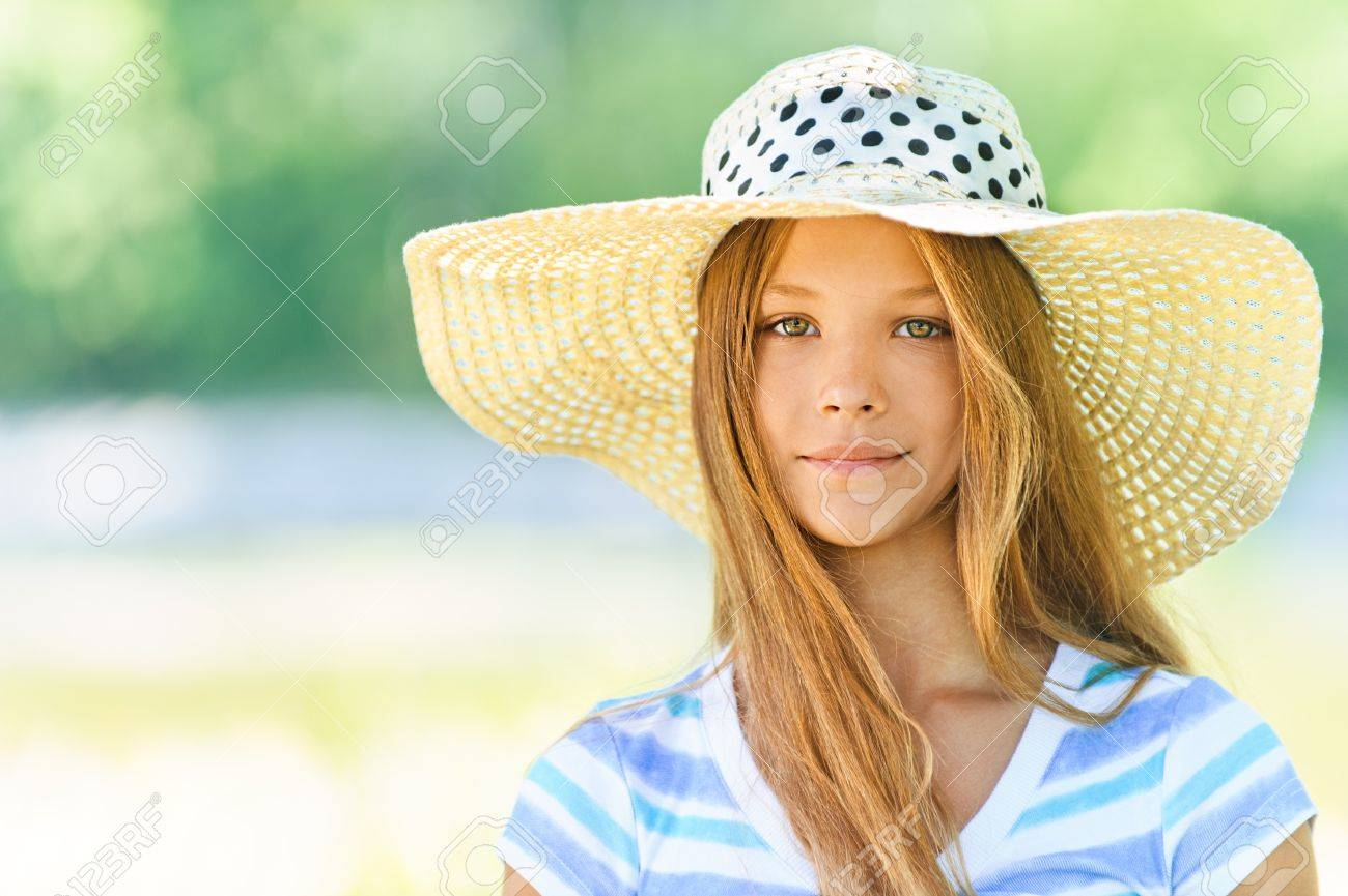 Portrait of smiling beautiful teenage in wide-brimmed hat, against green of summer park. Stock Photo - 15282481