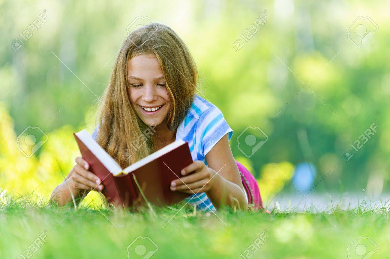 Beautiful smiling teenage girl in blue blouse lying on grass and read book, against green of summer park. Stock Photo - 15365824