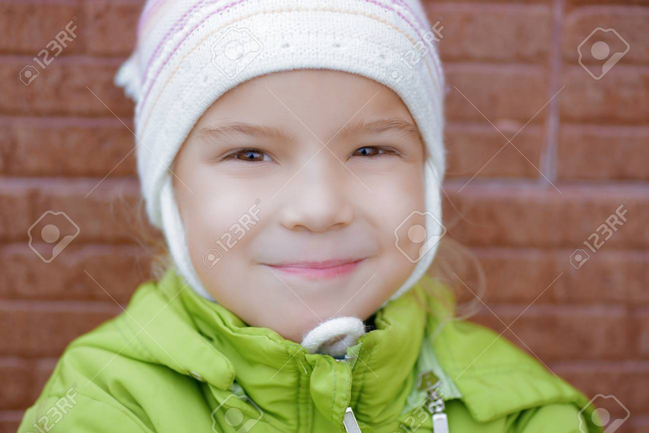 Beautiful smiling little girl in green jacket close-up against brick wall Stock Photo - 16062253