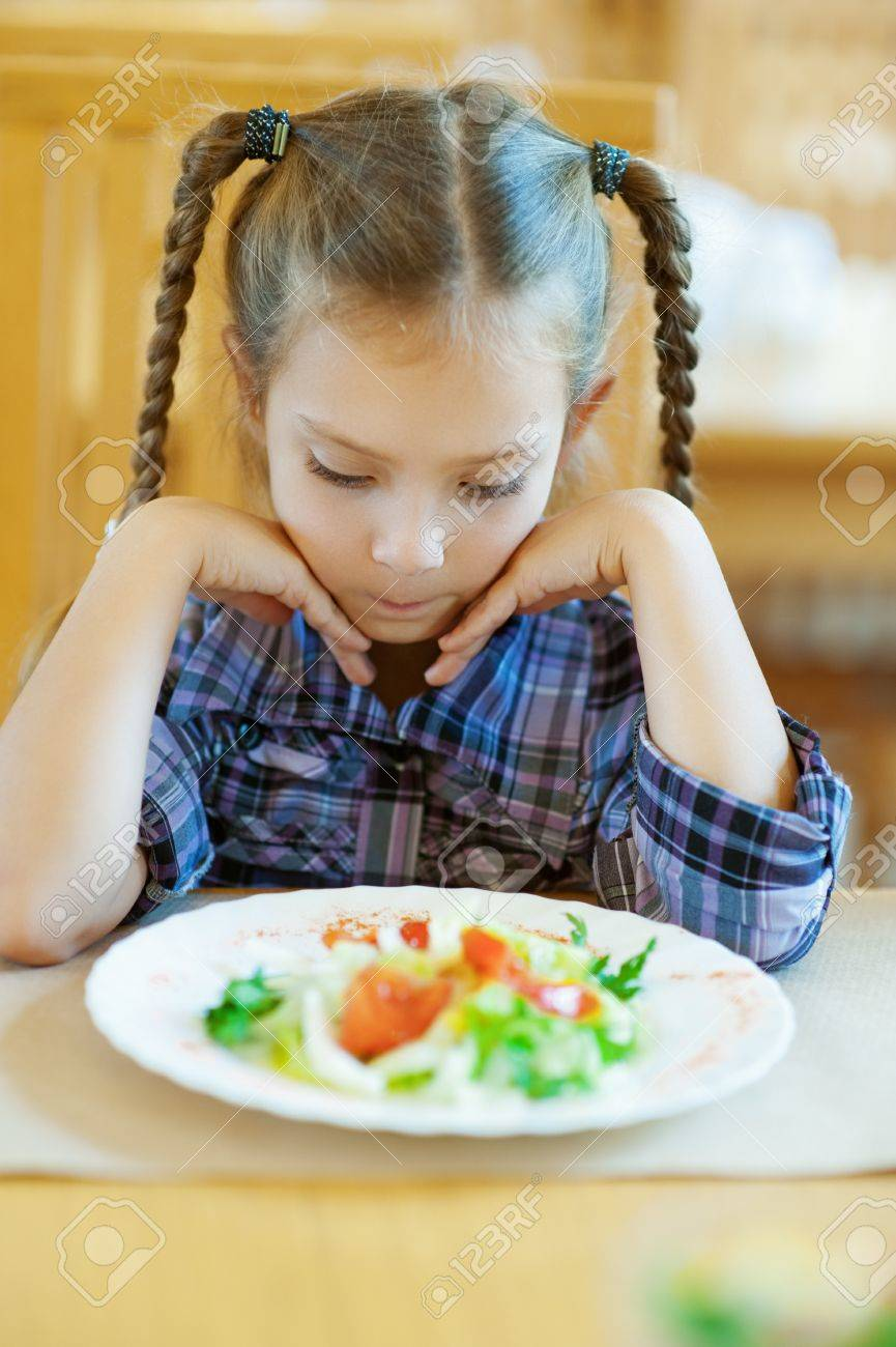 Beautiful little girl with pigtails sitting on table in restaurant and looks at prepared dish Stock Photo - 16639231